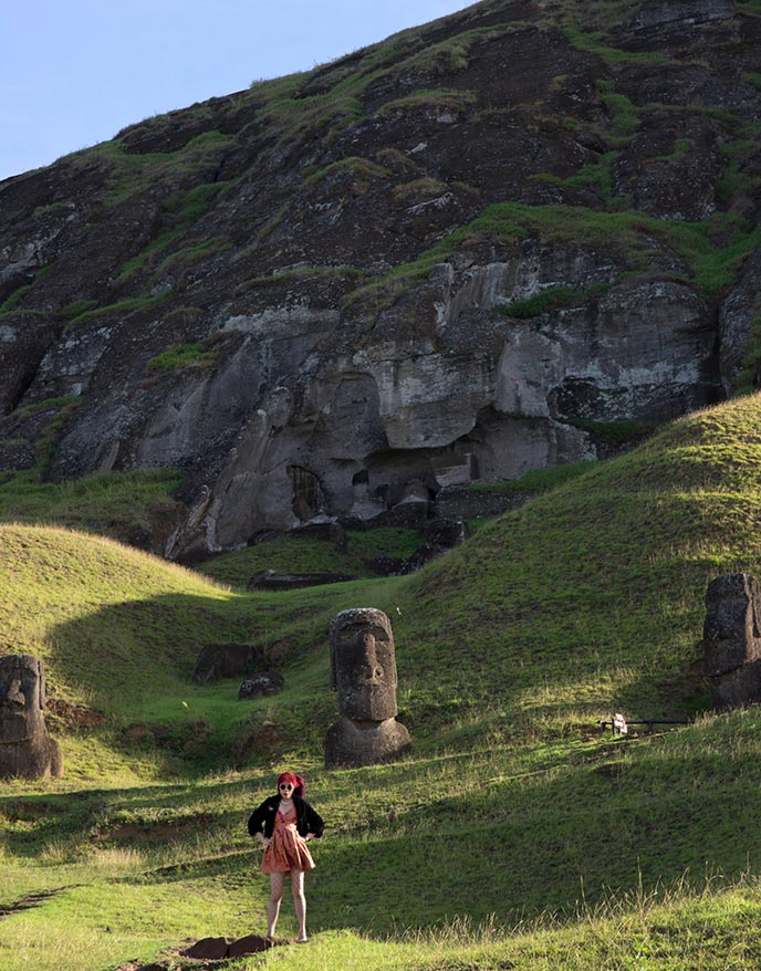 tourists posing with moai statue sculptures