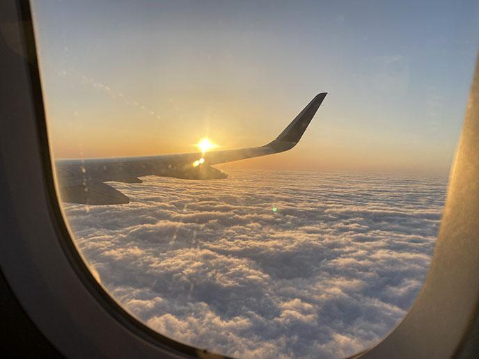 airplane wing sunset clouds window flight landing